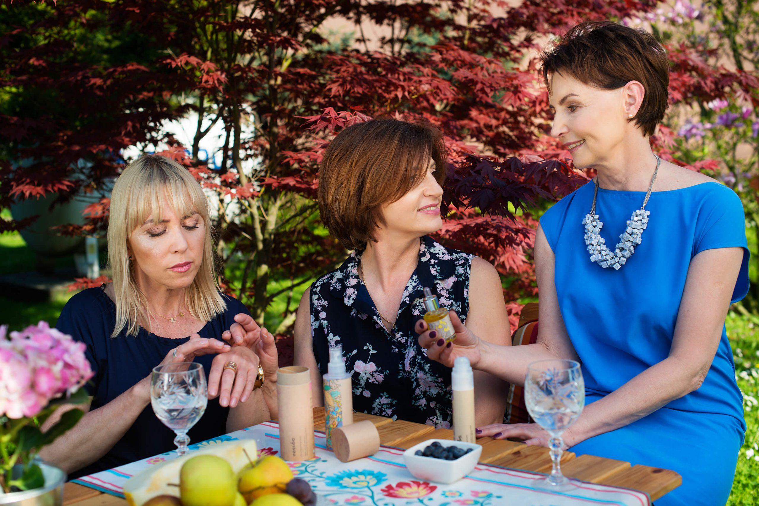 kosmetyki dla cery dojrzałej kobiety dojrzałe w ogrodzie testują kosmetyki i piją wodę