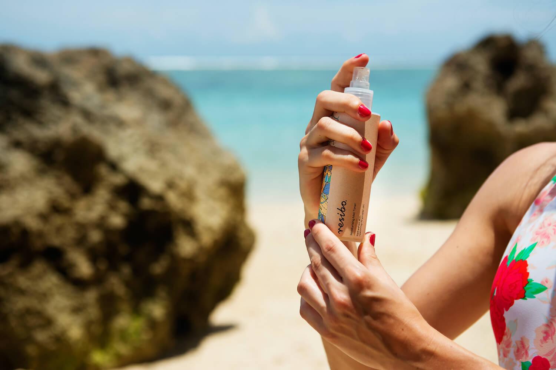kosmetyki nawilżajace a nawadniające dziewczyna trzyma tonik na tle morza