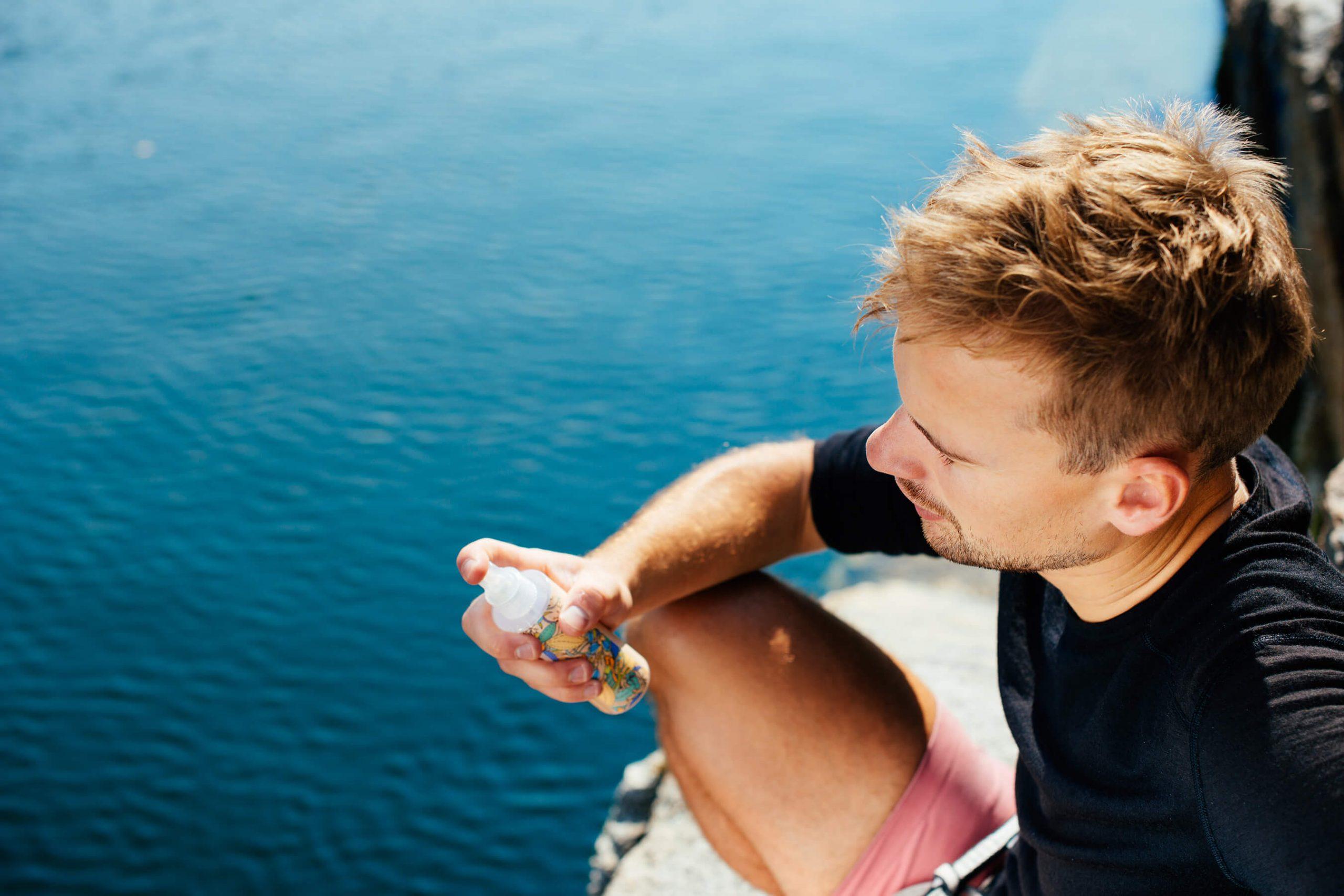 młody mężczyzna nad wodą trzyma tonik do twarzy resibo