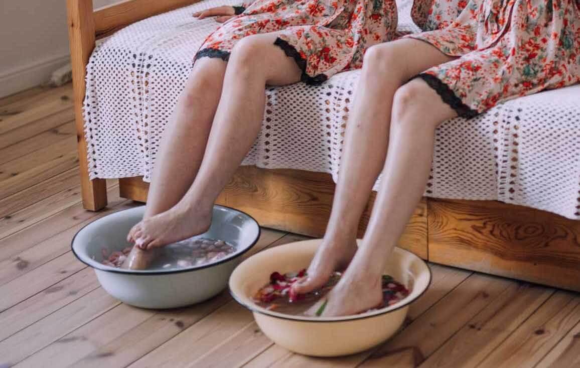 dwie kobiety w szlafrokach w kwiaty moczą nogi w miskach
