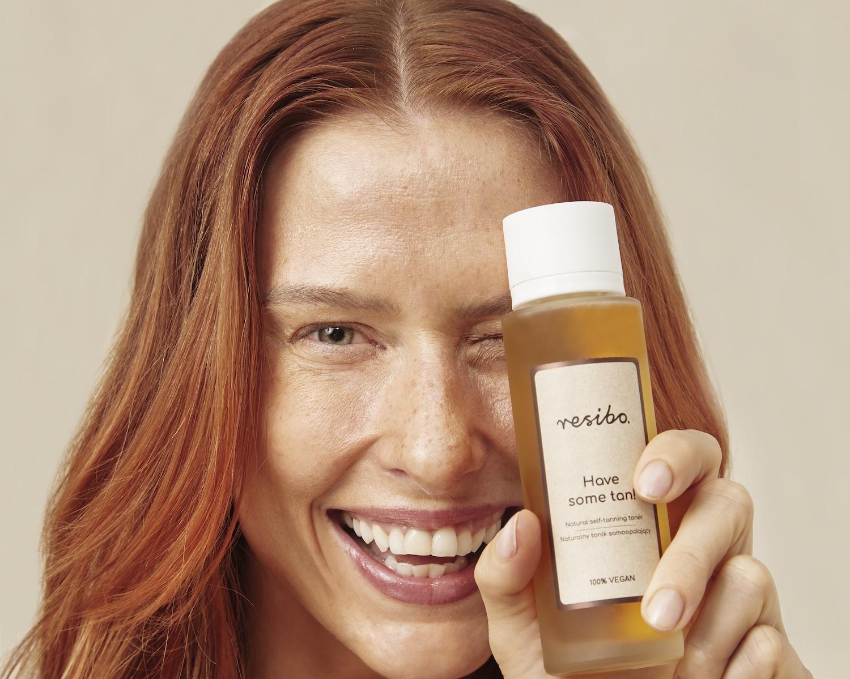 tonik samoopalający kobieta opalona ruda uśmiechnieta trzyma tonik