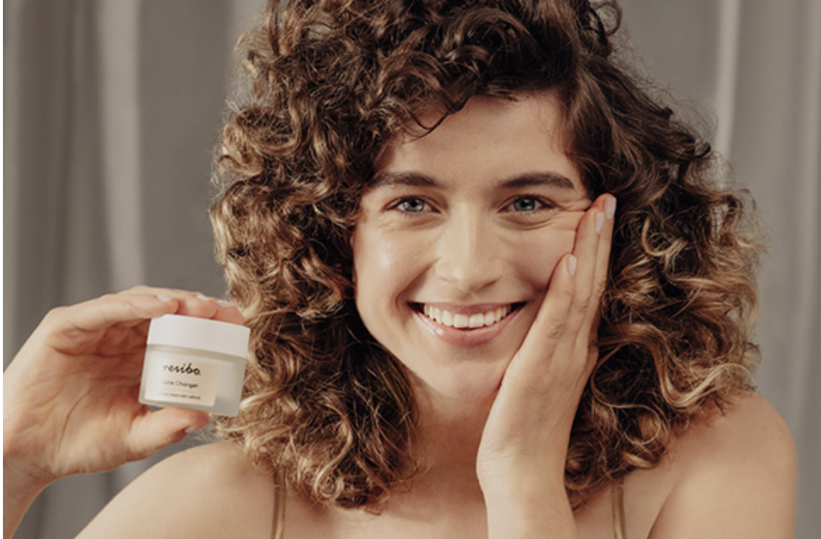 uśmiechnięta kobieta z kręconymi włosami prezentuje krem z retinolem w szklanym słoiczku