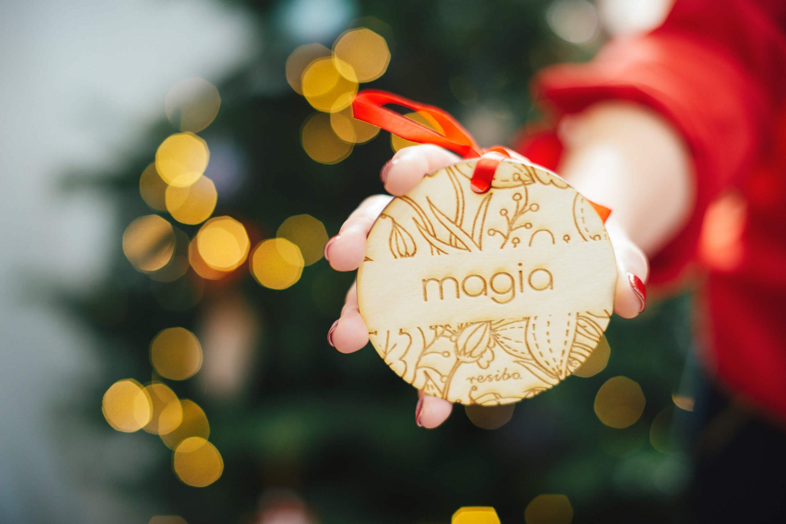 resibo drewniana ozdoba choinkowa z wypalonym napisem magia na tle choinki