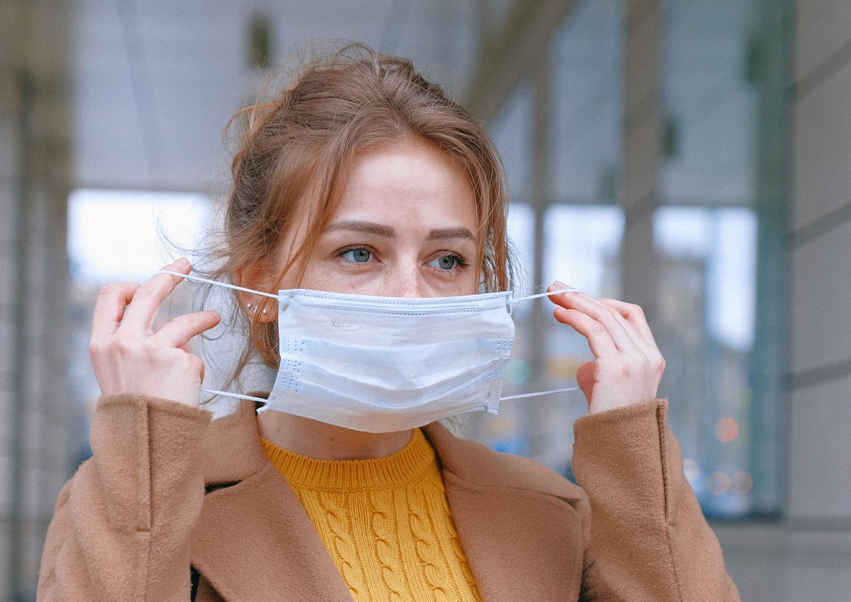 kobieta w płaszczu zakłada jednorazową maskę ochronną blog resibo