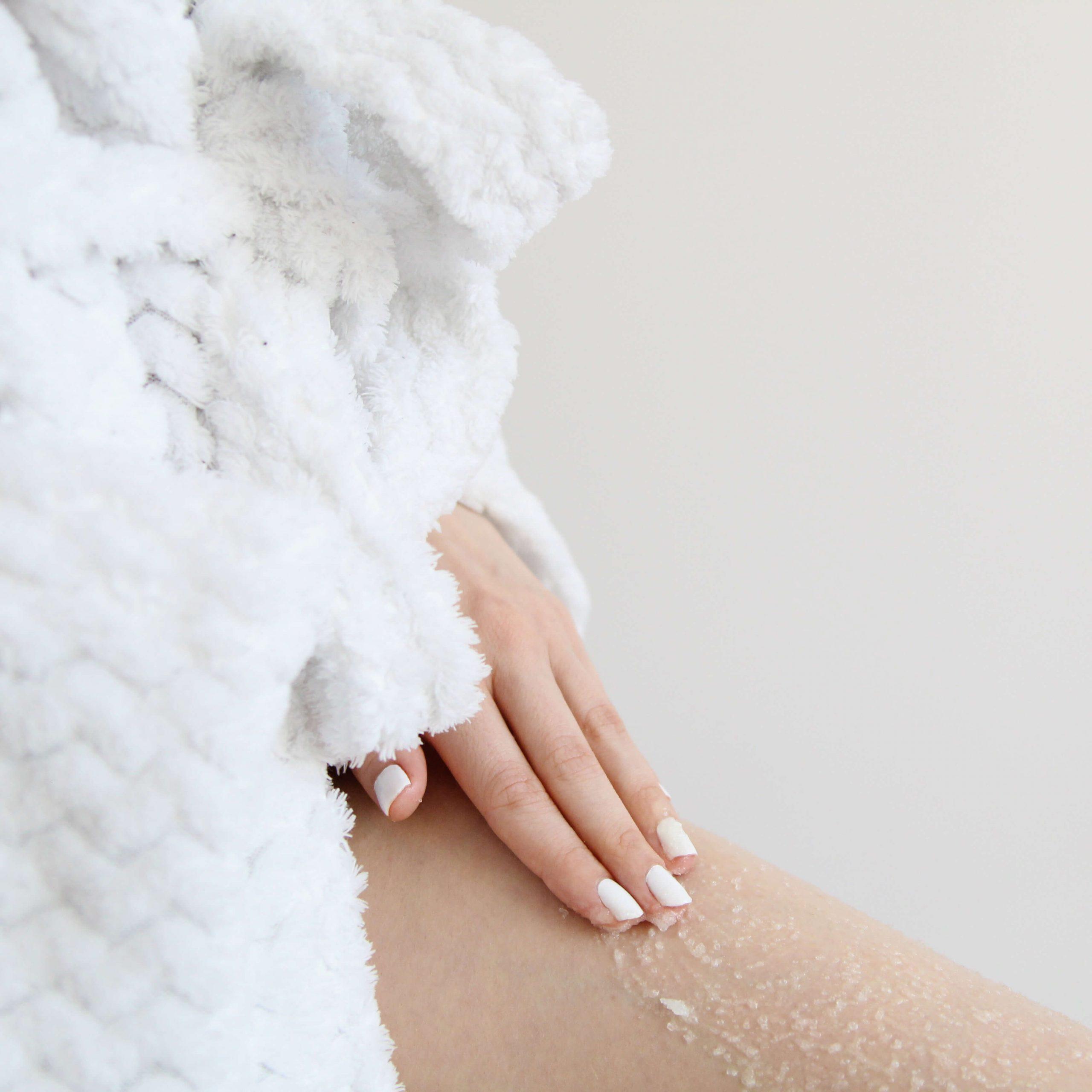 resibo peeling do ciała osoba w szlafroku dloń wciera peeling w ciało