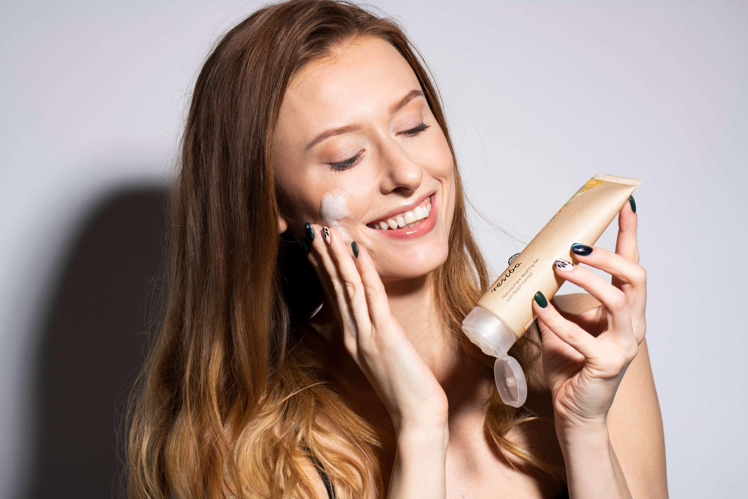 resibo_młoda kobieta uśmiechnięta trzyma w ręku żel myjący
