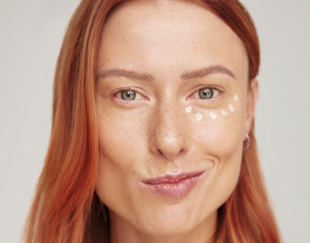 ruda kobieta z zabawnym uśmiechem i kropkami kremu pod jednym okiem