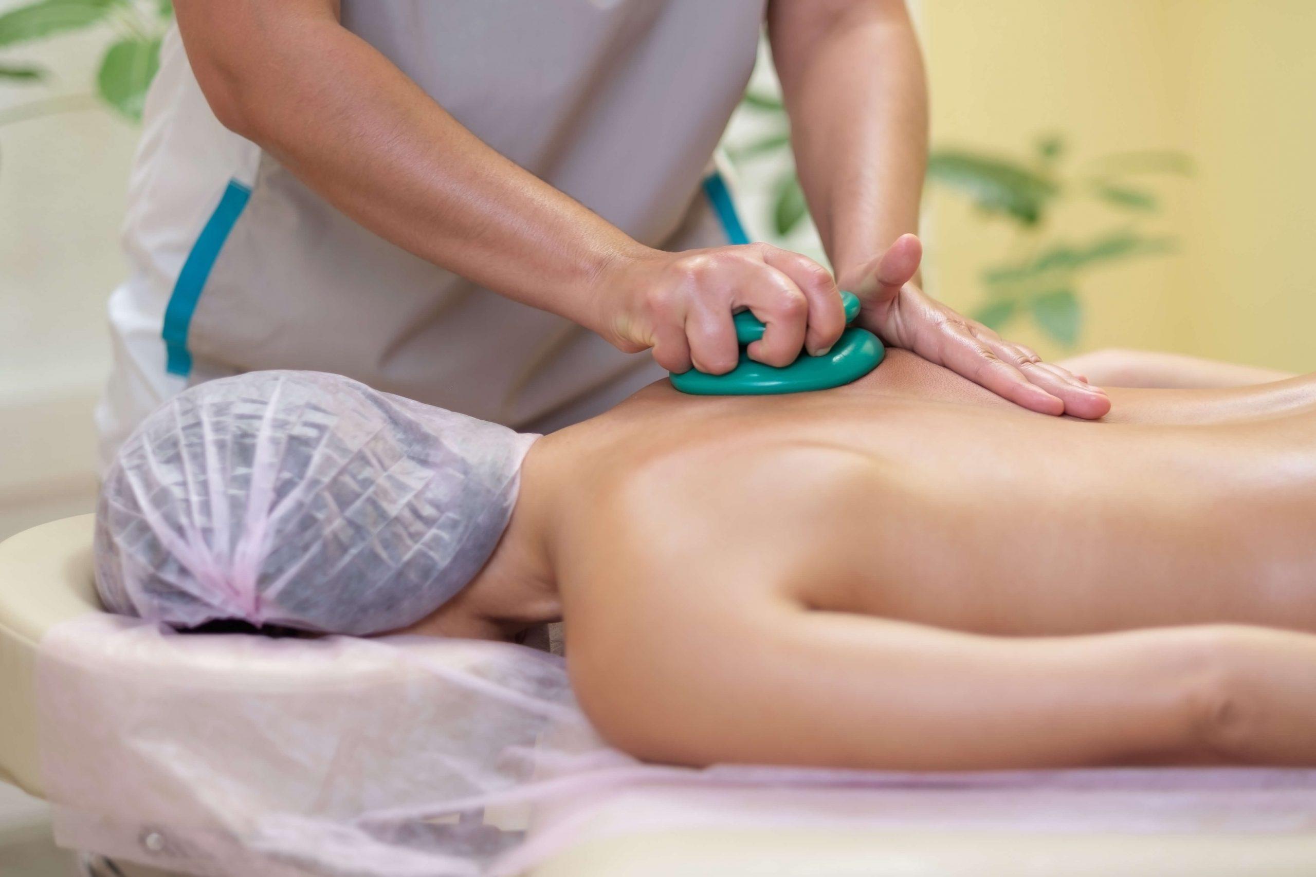 masażysta wykonuje masaż pleców bańką chińską