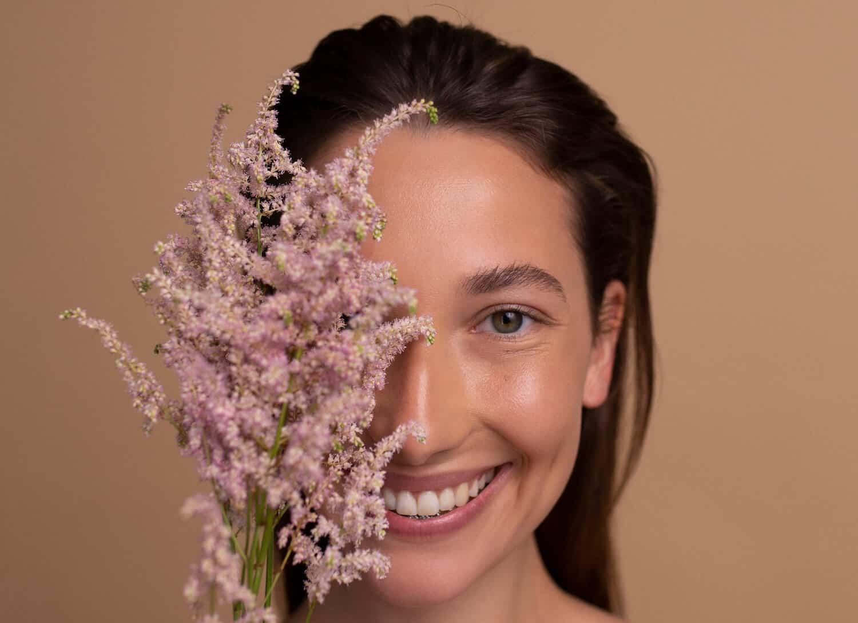 czy kosmetyki niszcza cere - blog resibo modelka usmiechnieta brunetka zaslania pol twarzy kwiatem