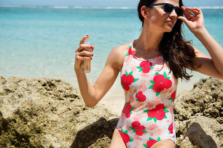 modelka na plazy w stroju w kwiaty i ciemnych okukularach odswieza cialo - bezpieczne dezodoranty blog resibo