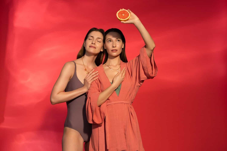 dwie kobiety brunetki na ceglastym tle oslaniaja sie przed sloncem jedna trzyma w rece plaster grejpfruta
